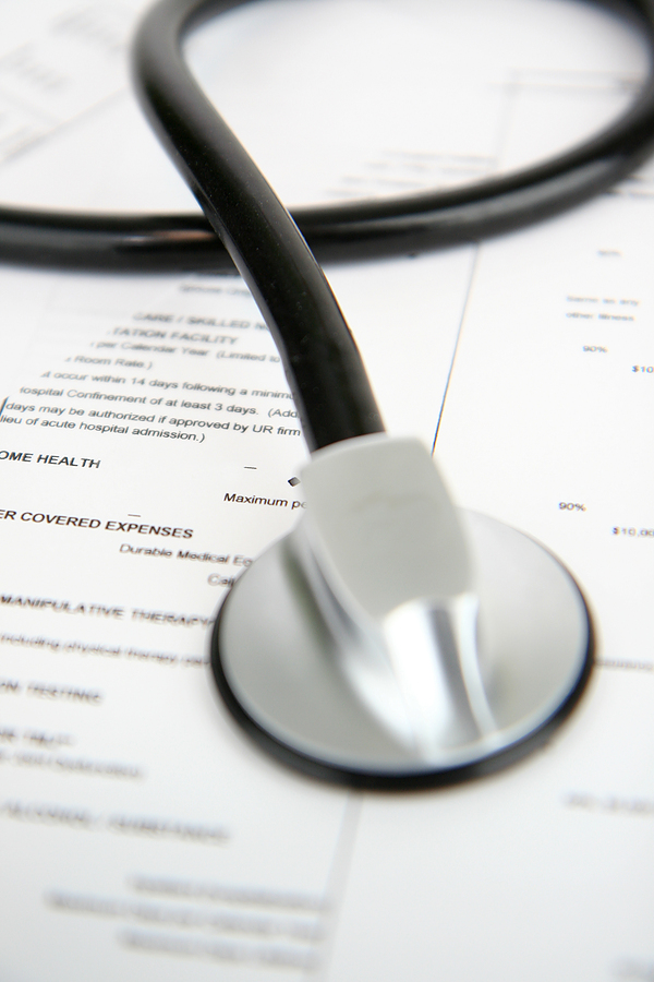 a stethescope on health insurance documents